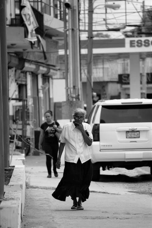 Foto d'estoc gratuïta de adult, blanc i negre, caminant, carrer