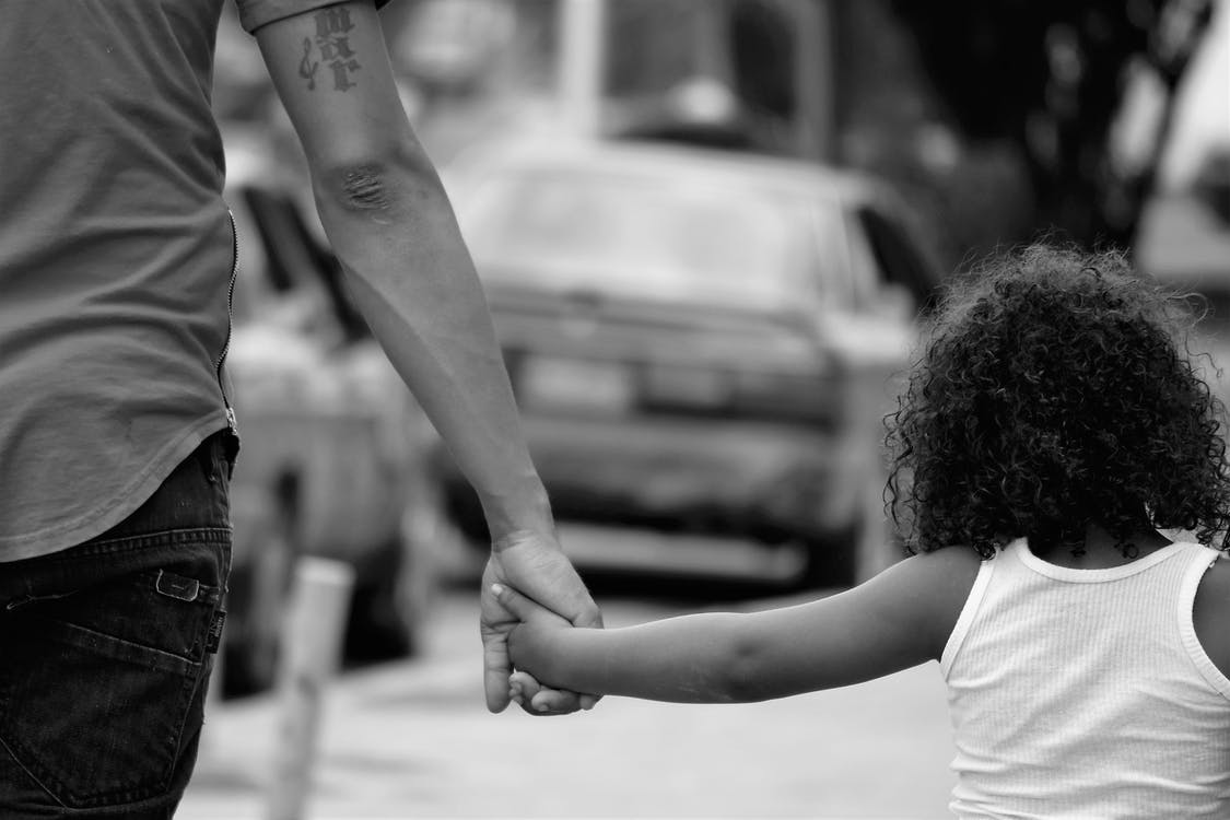 Grayscale Photography of Father and Daughter Holding Each Other While Walking