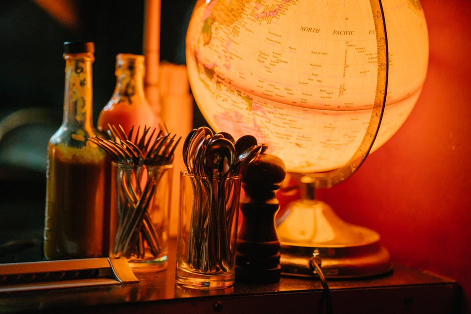 Lighted desk globe beside condiment shaker and flatware set