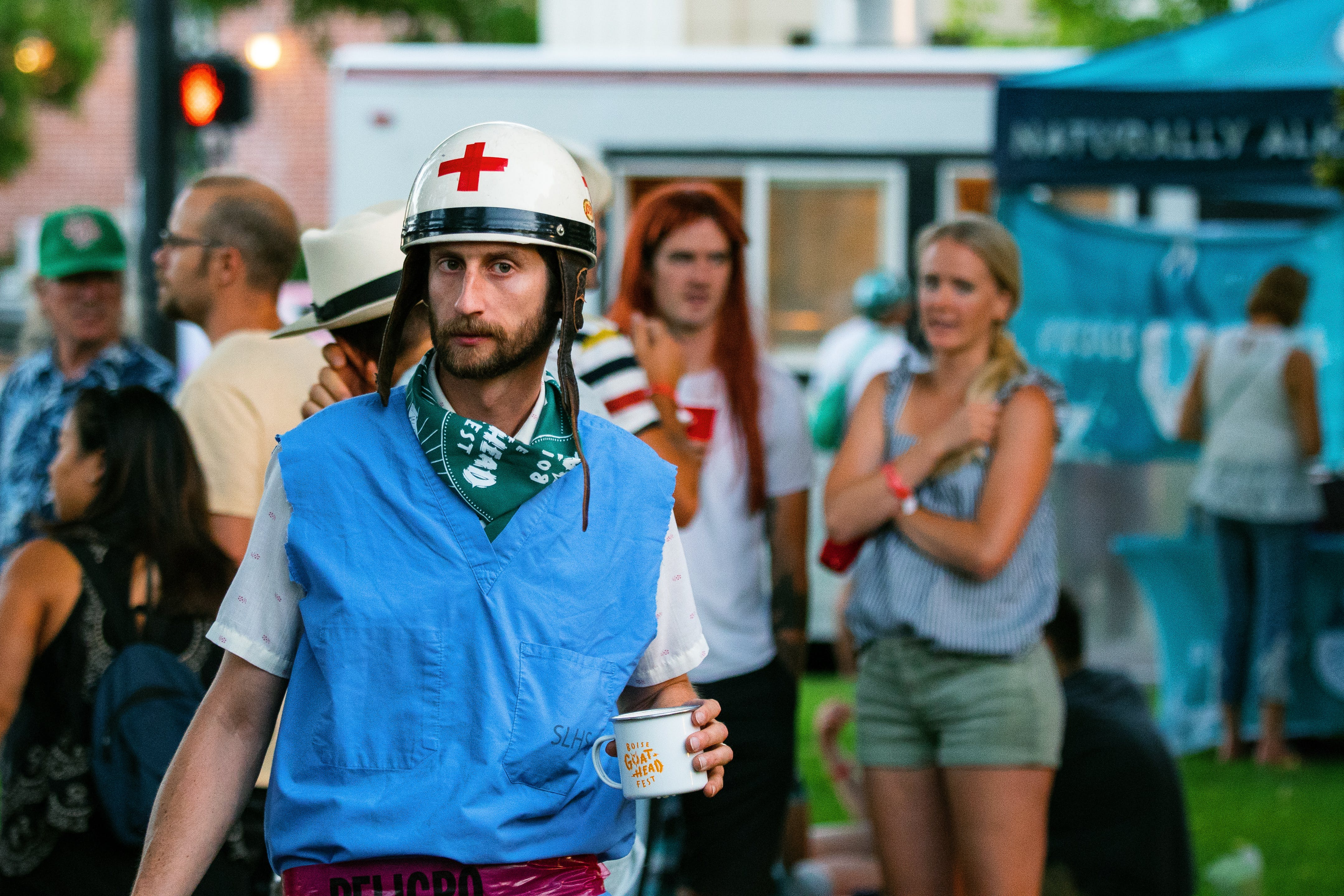 Man Holding Cup in a White Helmet with a Red Cross Near Group of People