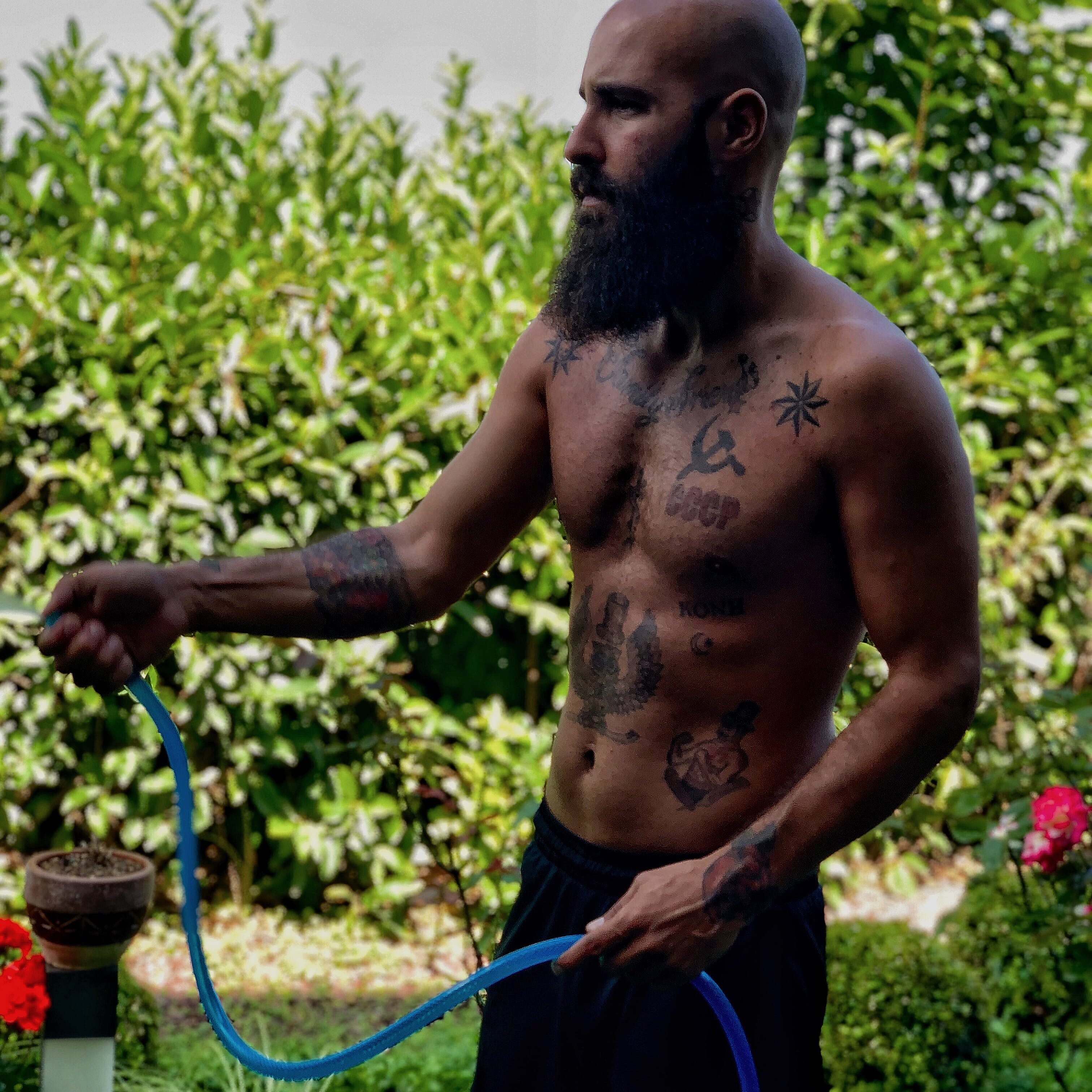 Shallow Focus Photography Of Topless Man Holding Water Hose