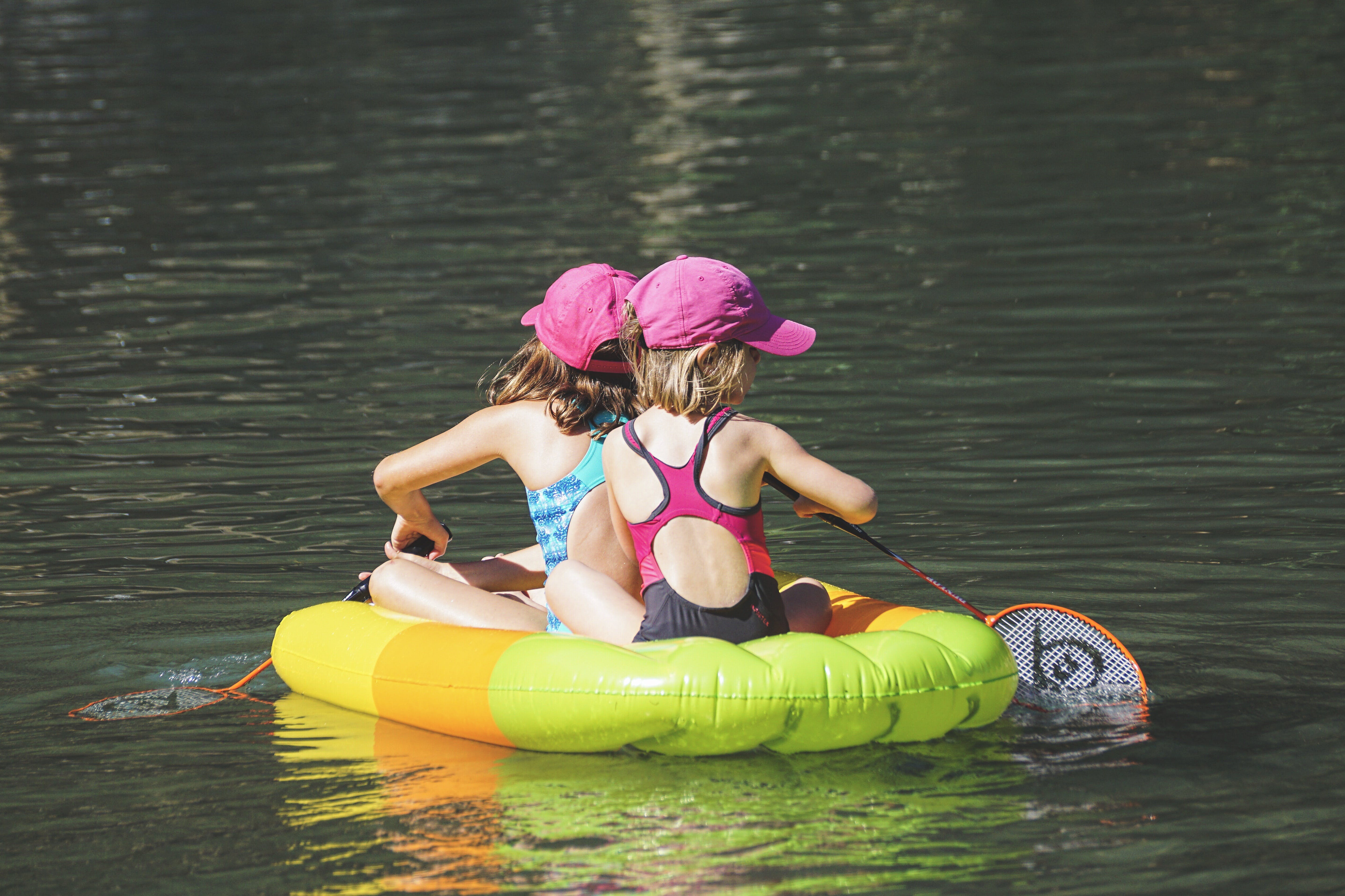 Two Girls in Floating and Paddling Using Badminton Rackets