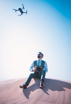 Man Sitting on Desert Ground Looking Up and Operating the Quadcopter