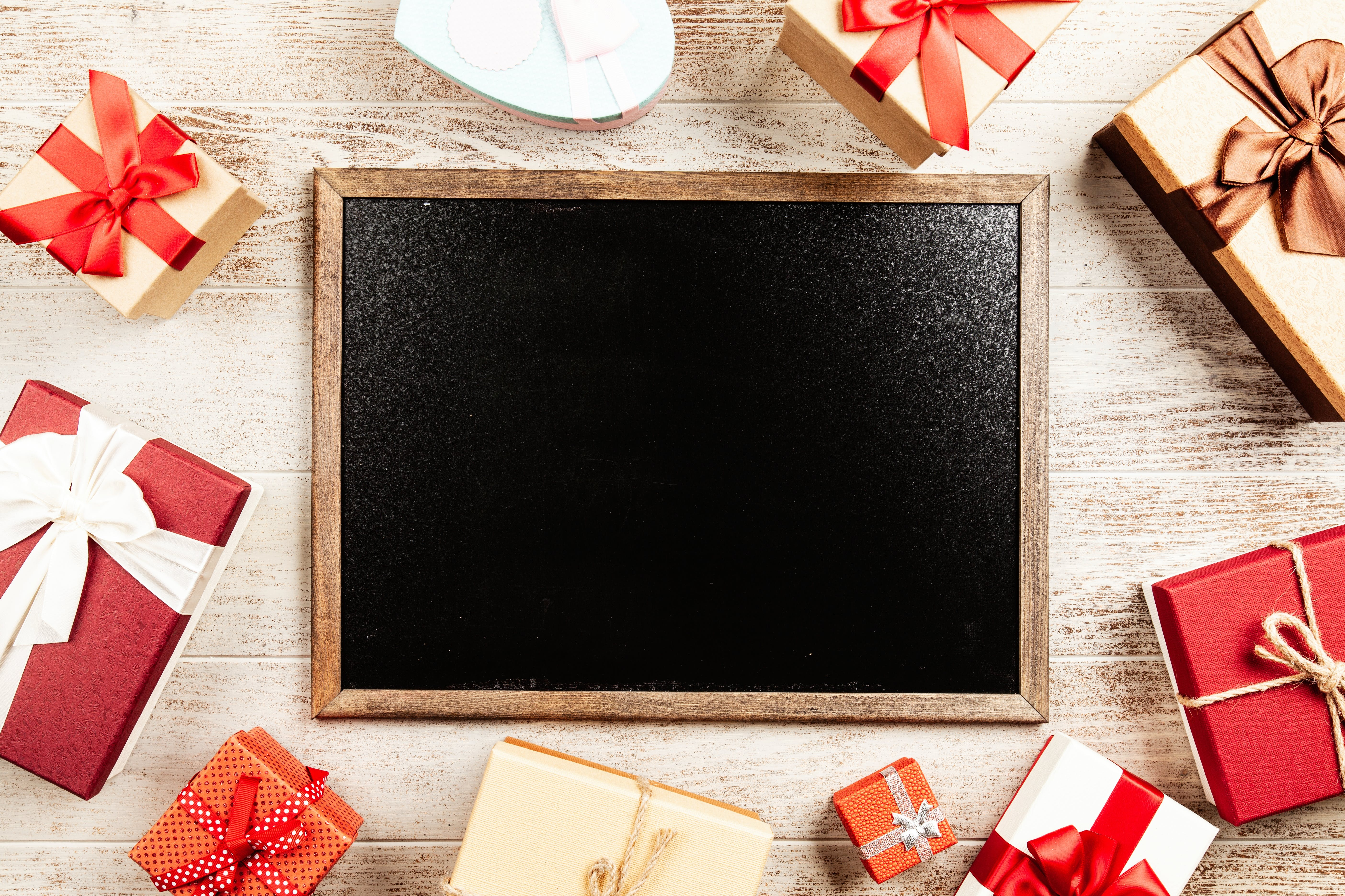 Chalkboard With Brown Wooden Frame Surrounded by Red Gift Boxes