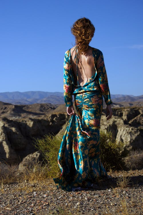 Woman Wearing Blue and Multicolored Floral Backless Long-sleeved Dress Standing in Front of Rock Formation