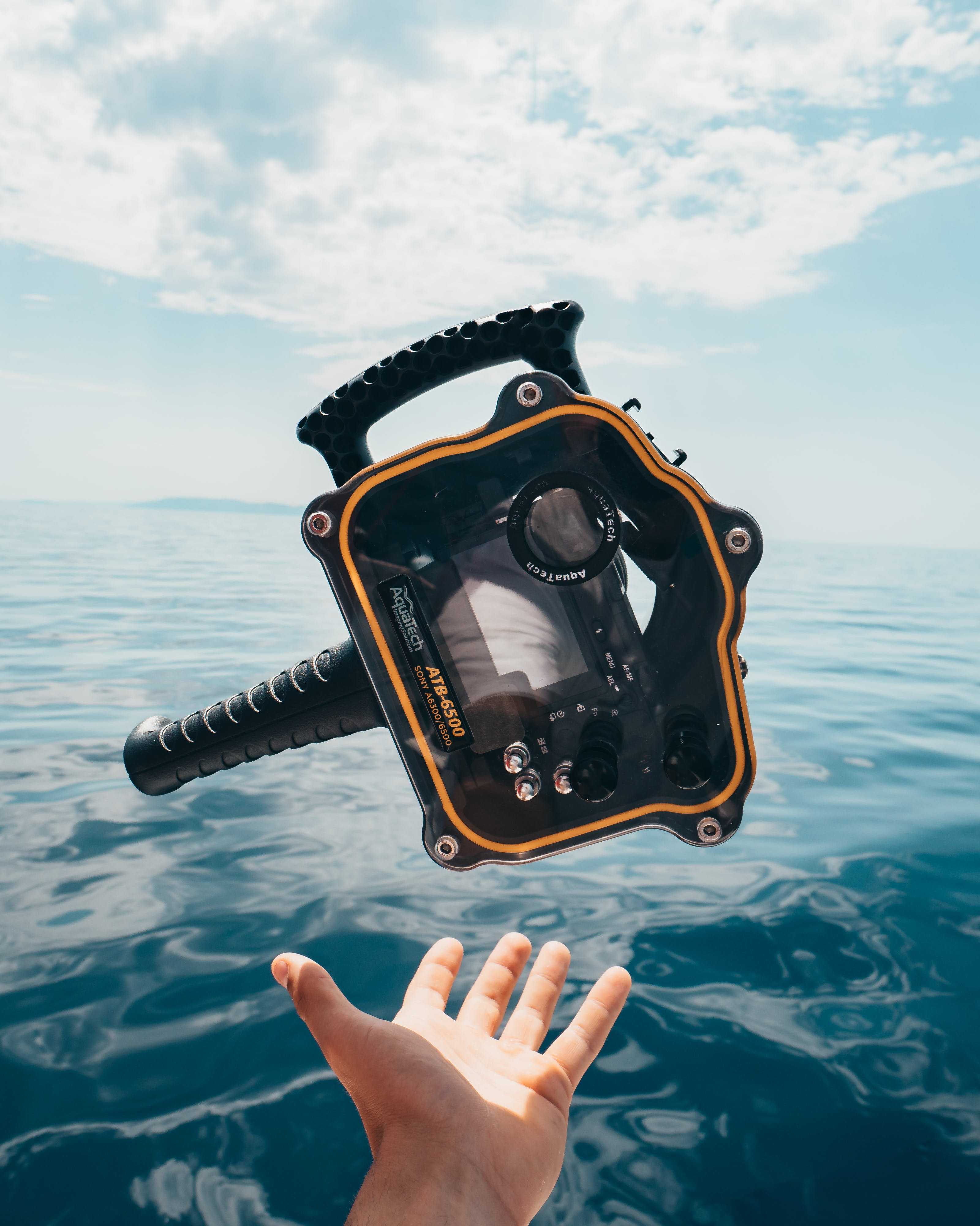 Person Grabbing Black and Orange Plastic Case Front of Calm Water