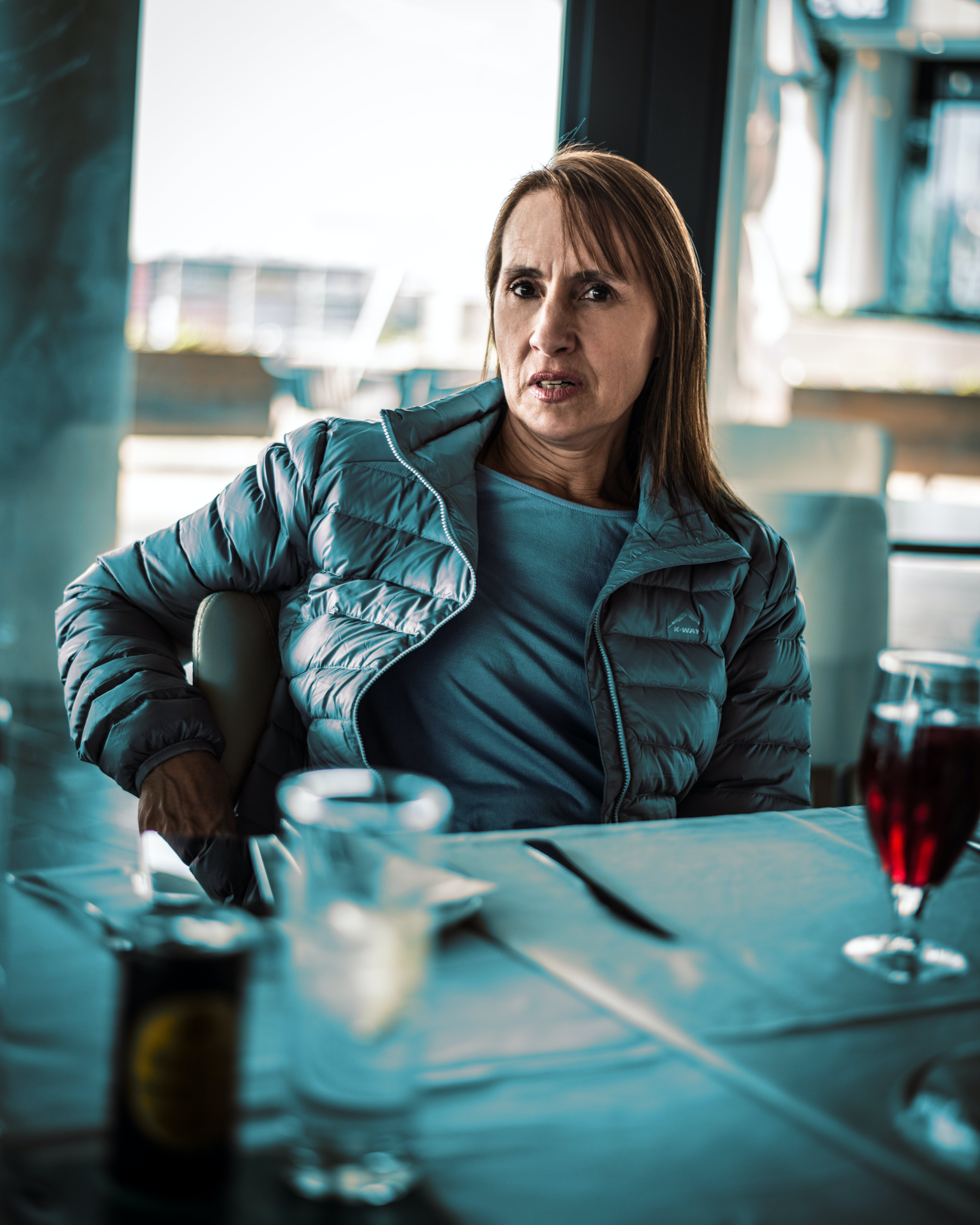 Woman in Blue Jacket Sitting in Front of Set Table