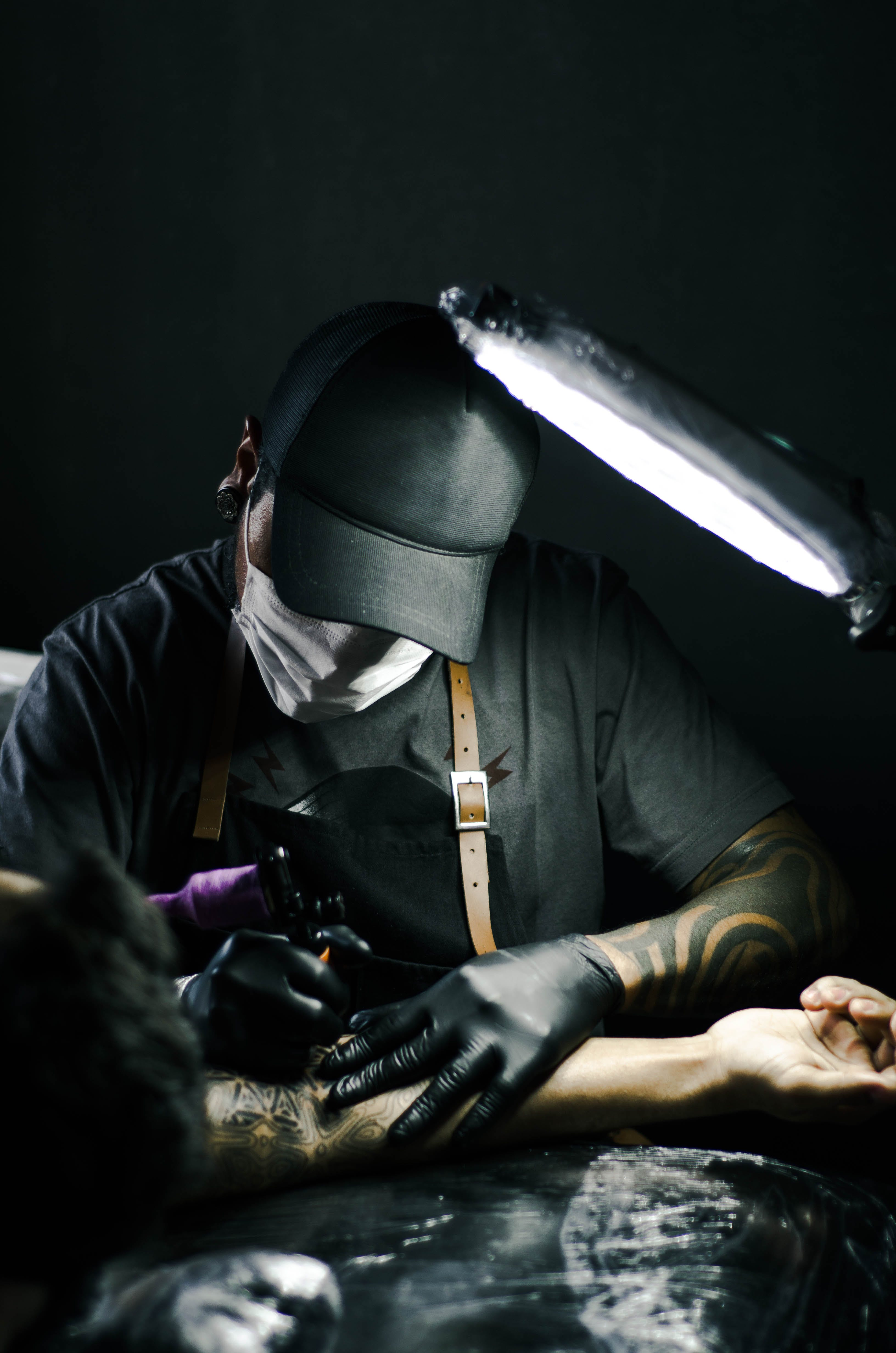 Tattoo artist in black gloves drawing a tattoo on a person's arm