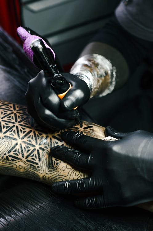 Selective Focus Photography of Tattoo Artist Drawing A Tatoo