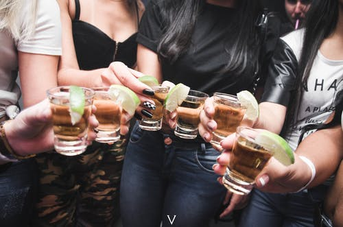 Women Holding Shot Glasses