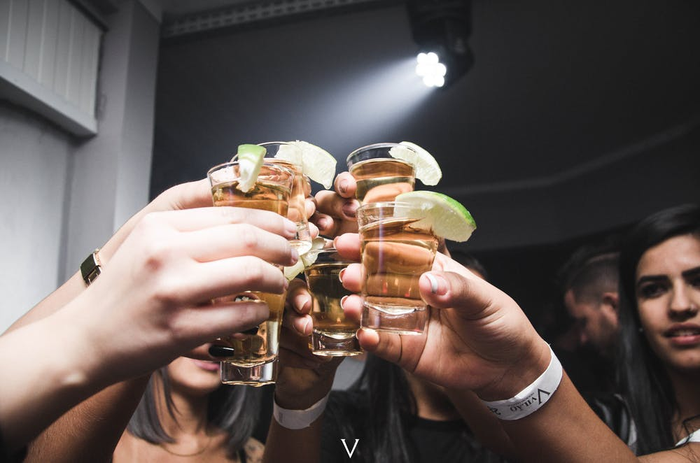 People doing cheers at a bar. | Photo: Pexels