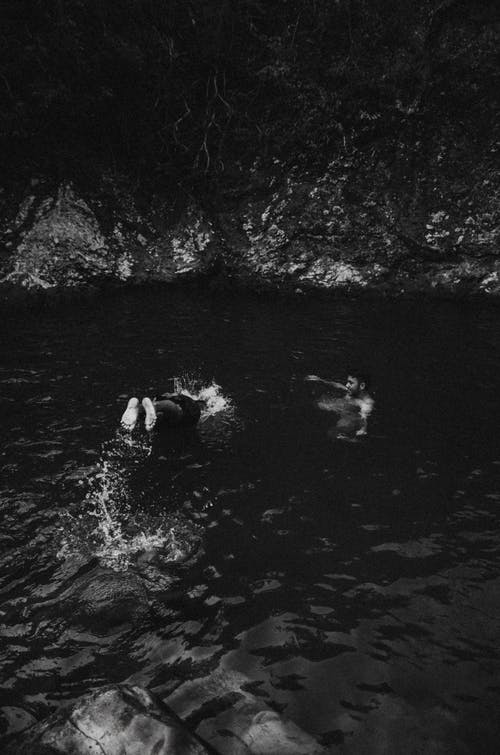 Grayscale Photo of People Swimming