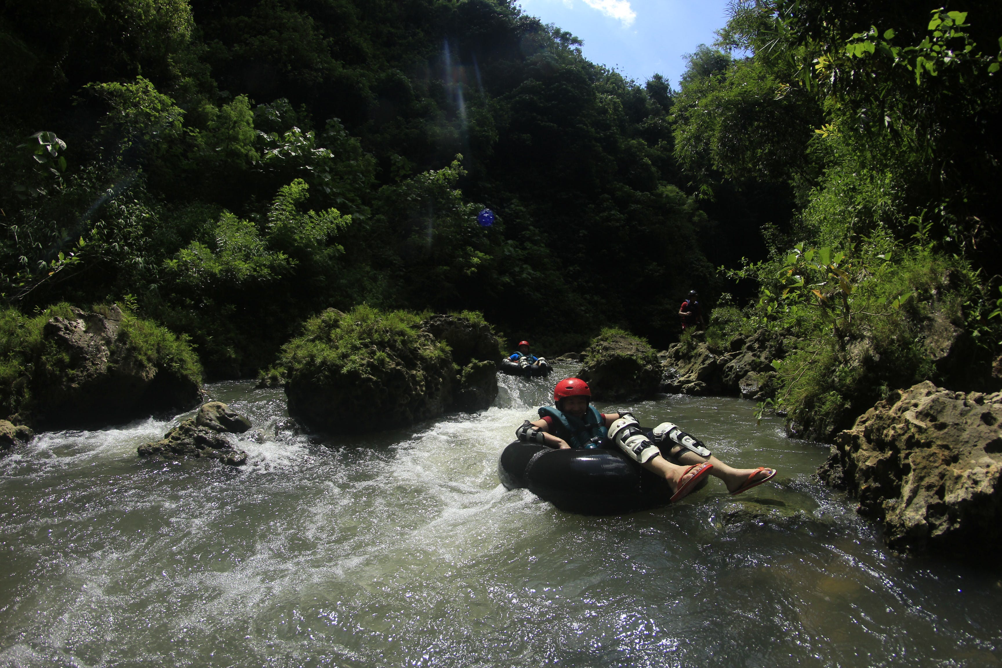 Person Riding Black Inflatable Ring on Body of Water Near Mountain