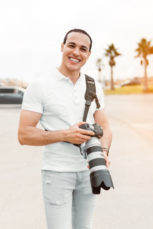 Shallow Focus Photography Of Man Standing While Holding Dslr Camera