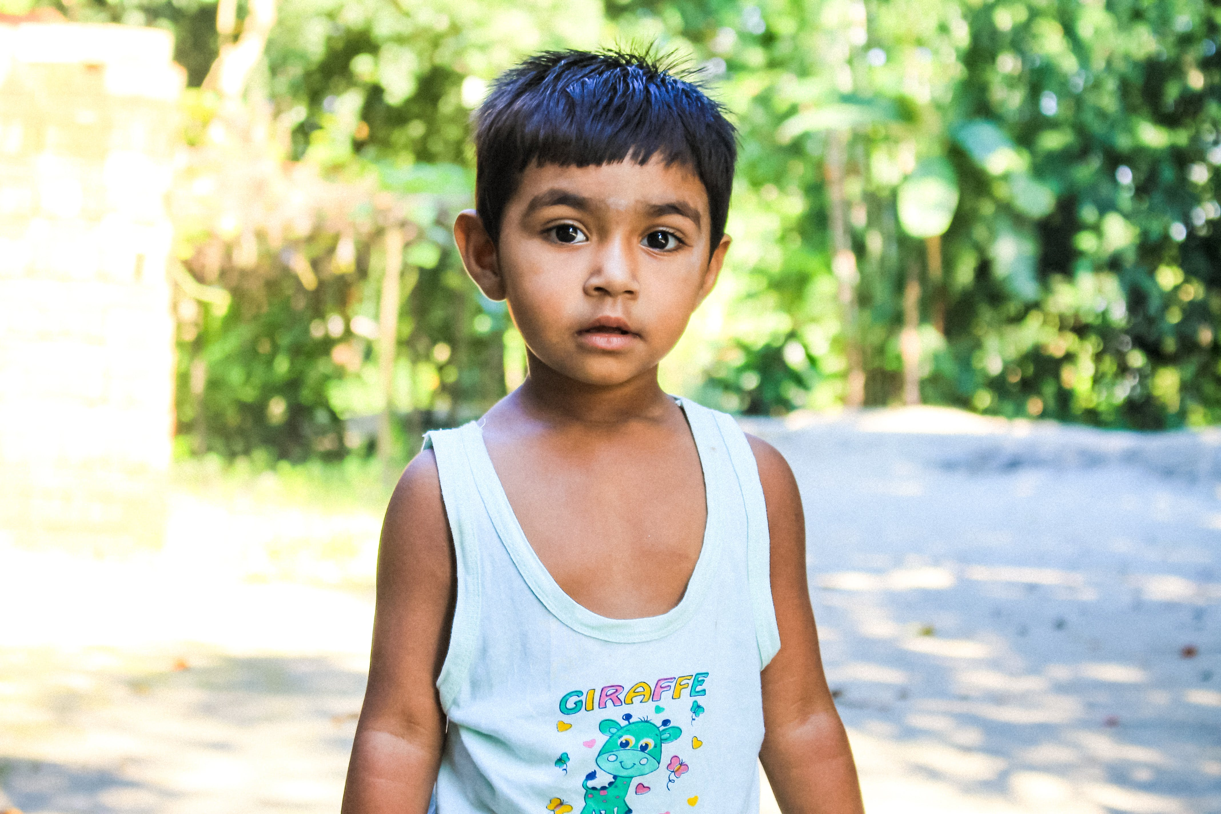 Boy in White Tank Top Standing on Focus Photo