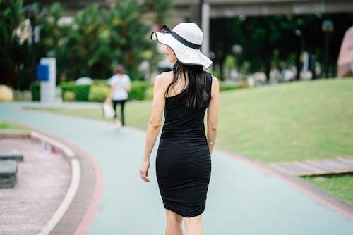 Foto profissional grátis de andando, cabelo, caminho asfaltado, chapéu