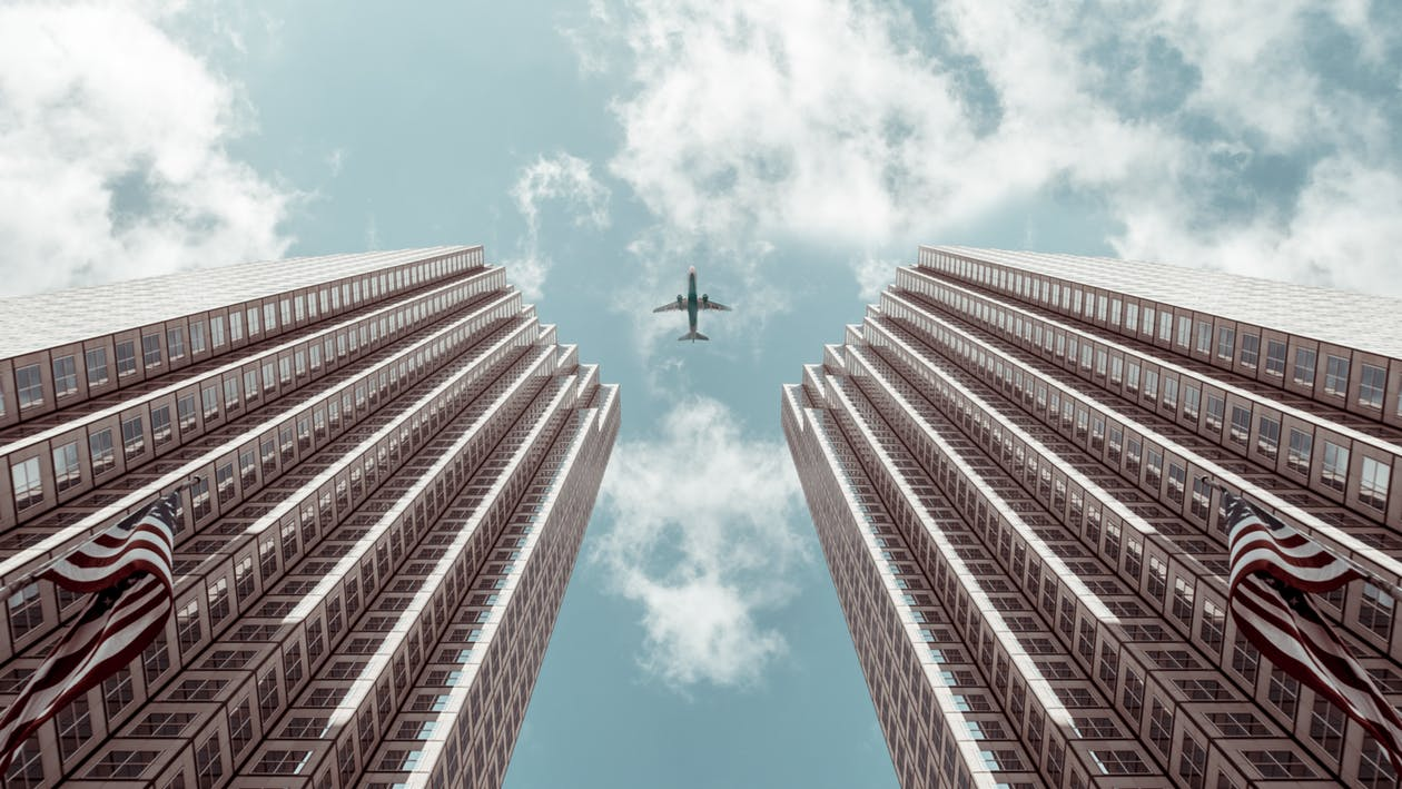 Worm's-eye view Photo of Plane Between Two High-rise Buildings