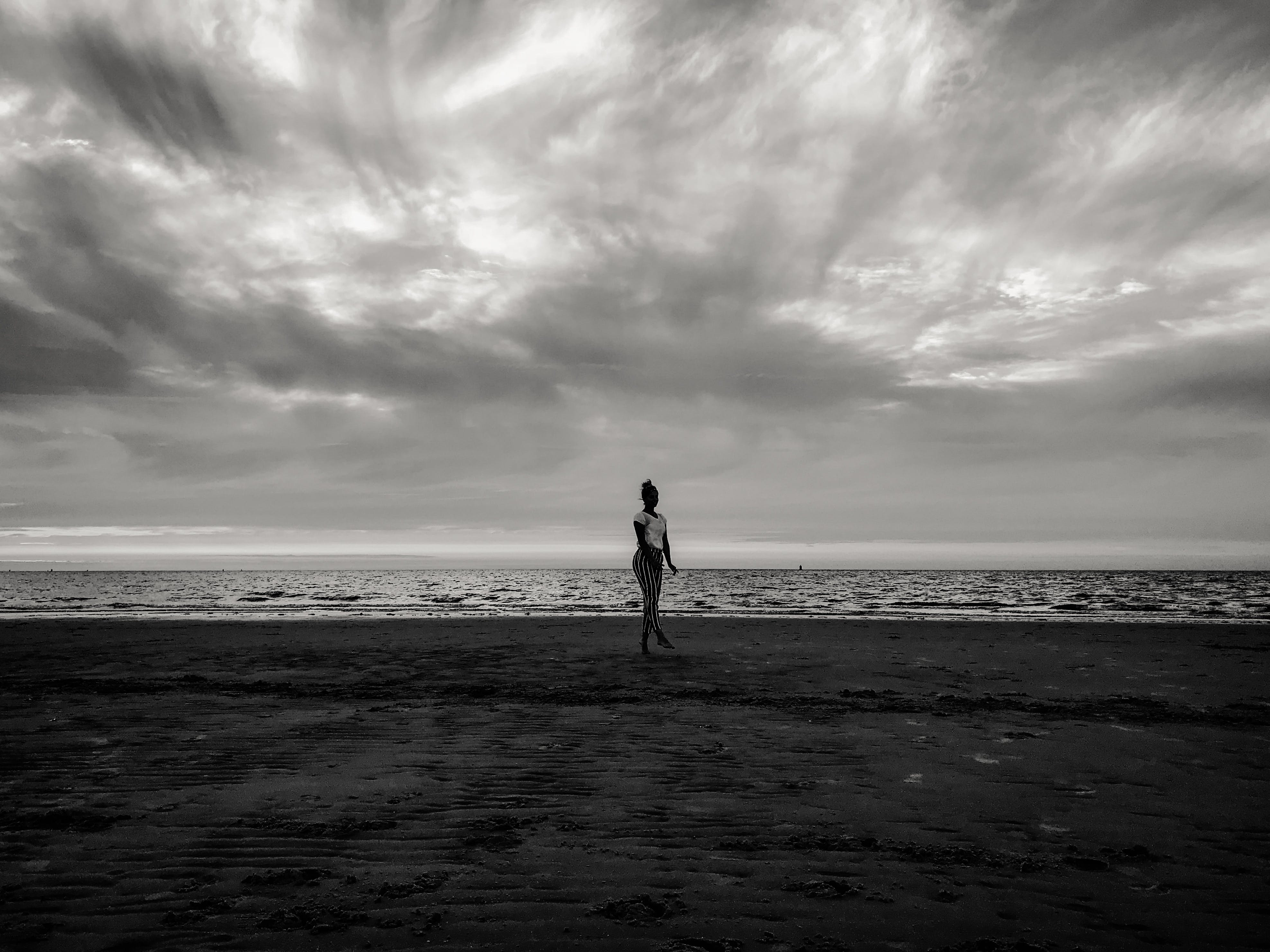 Person Standing on Seashore Under Cloudy Sky