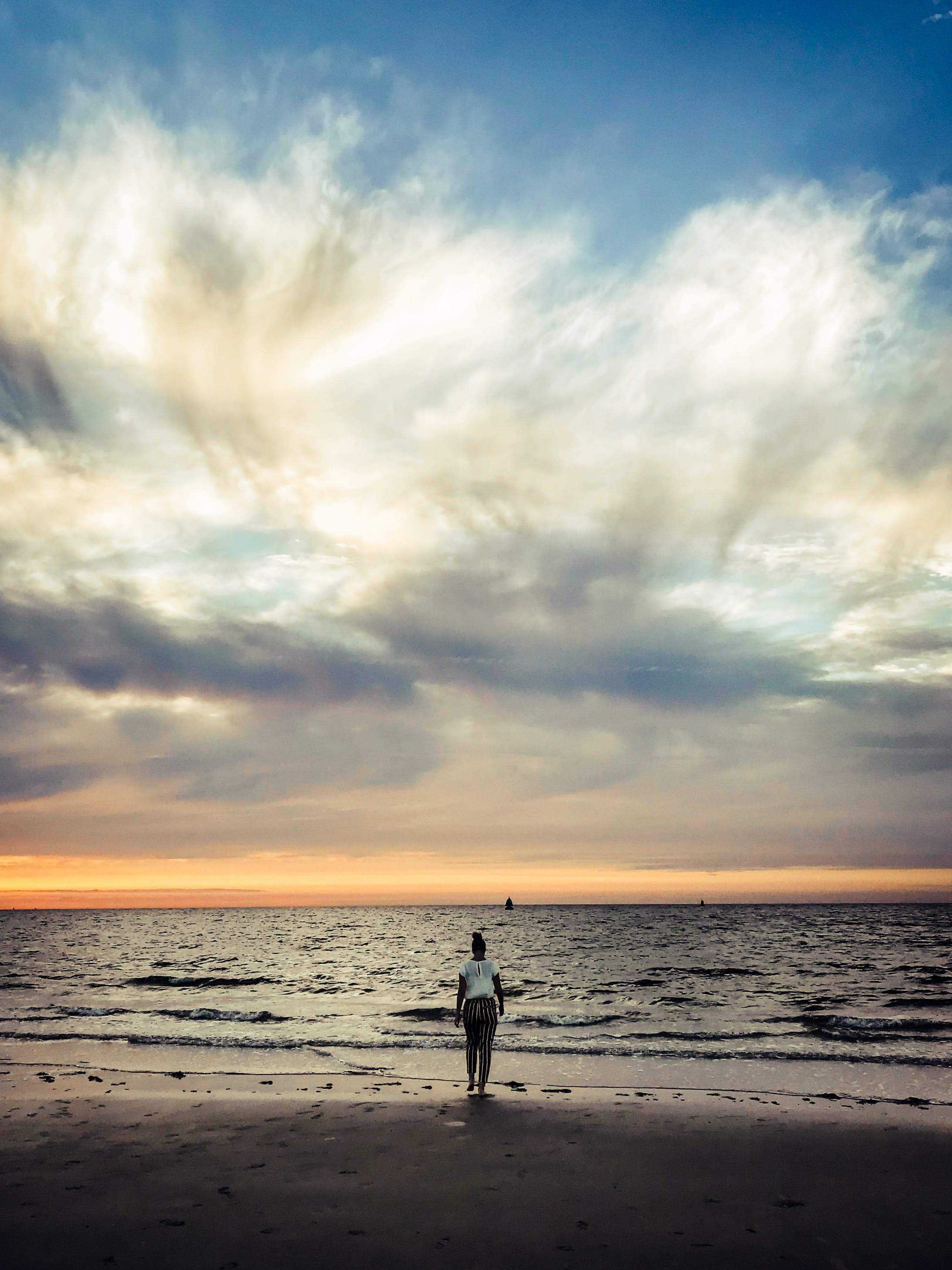 Person Standing Beside Seashore Under White Clouds during Golden Hour