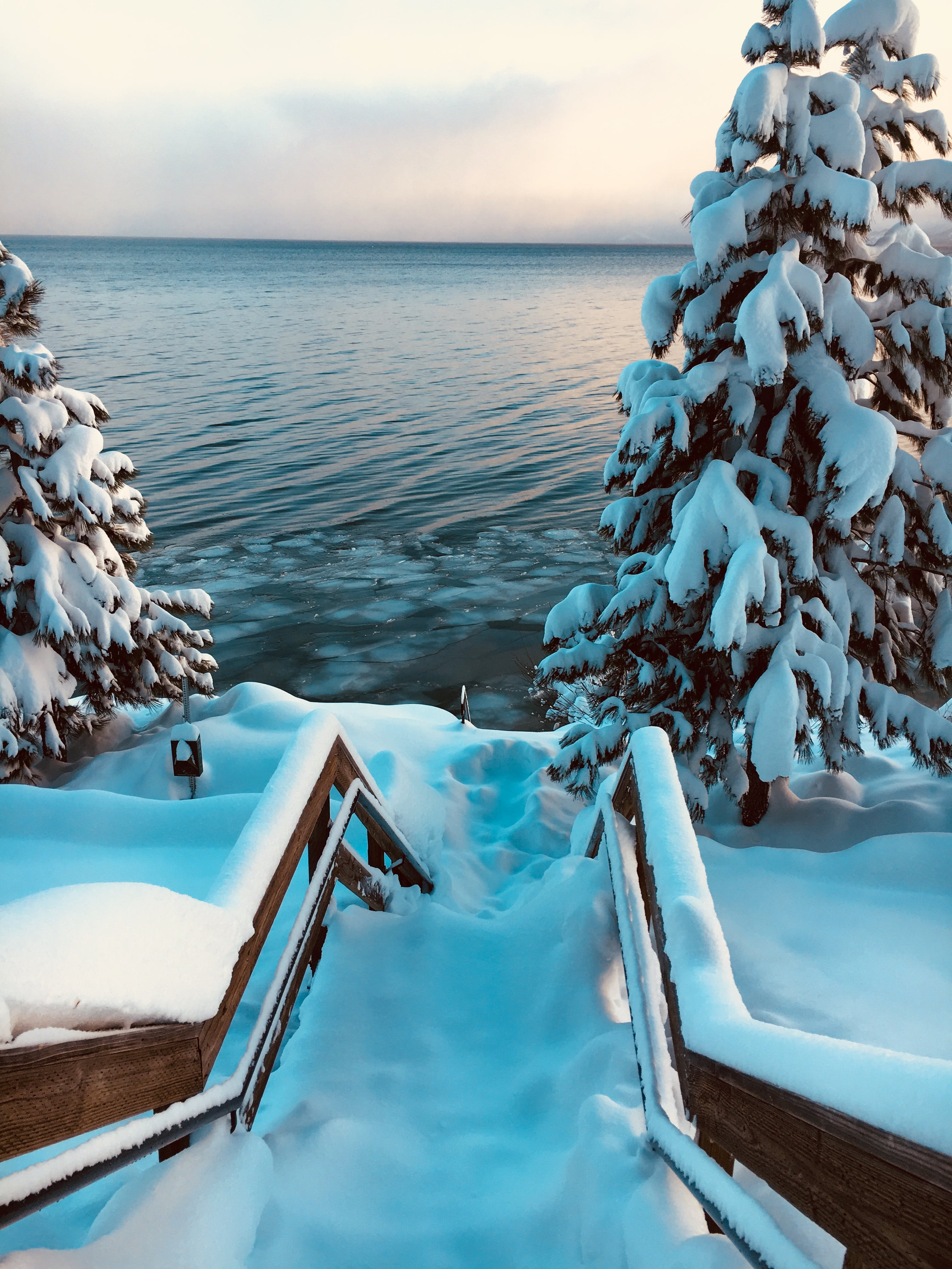 Snow Covered Stairs Near Body of Water