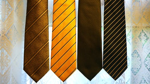 Four Assorted-color Neckties on Gray Textile