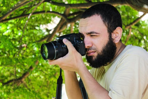 Man in Beige Shirt Taking Photo Using Black Dslr Camera Beside Tree