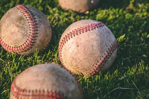 Close Up Photography of Four Baseballs on Green Lawn Grasses