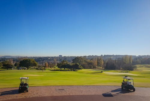 Two Golf Carts on Field Under Blue Sky