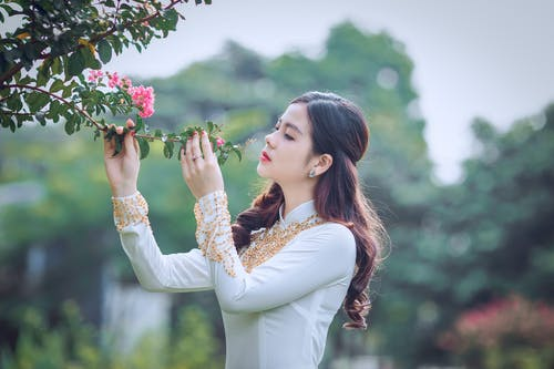 Shallow Focus Photography Of Woman Smelling Flower