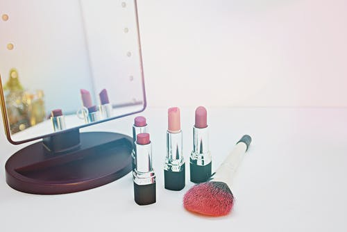 Four Assorted-color Lipsticks Beside Makeup Brush