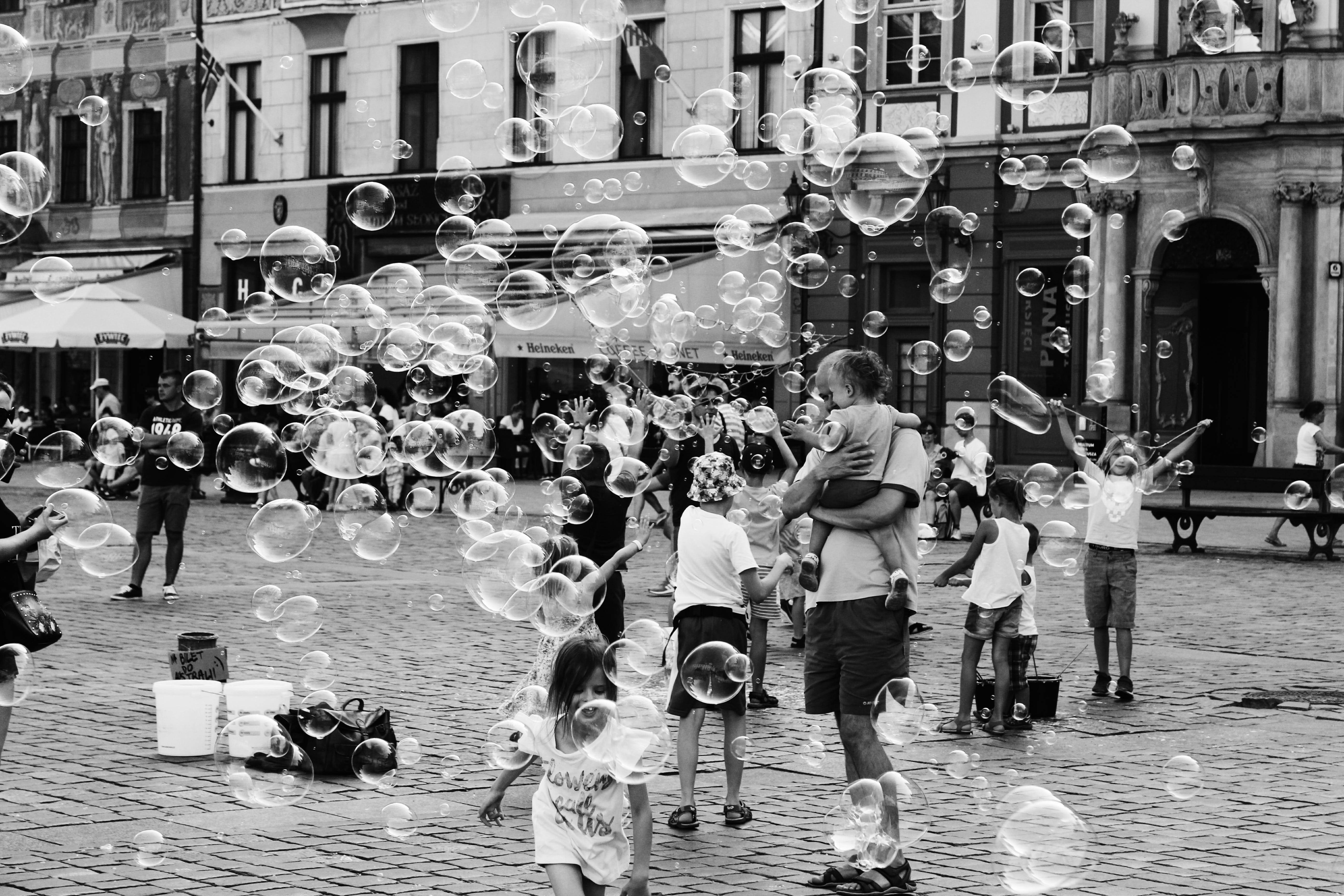 Grayscale Photo of Children and Parents Outdoors With Bubbles