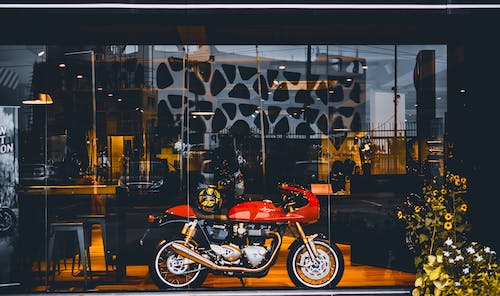 Red Standard Motorcycle With Gold Helmet Near Glass Wall