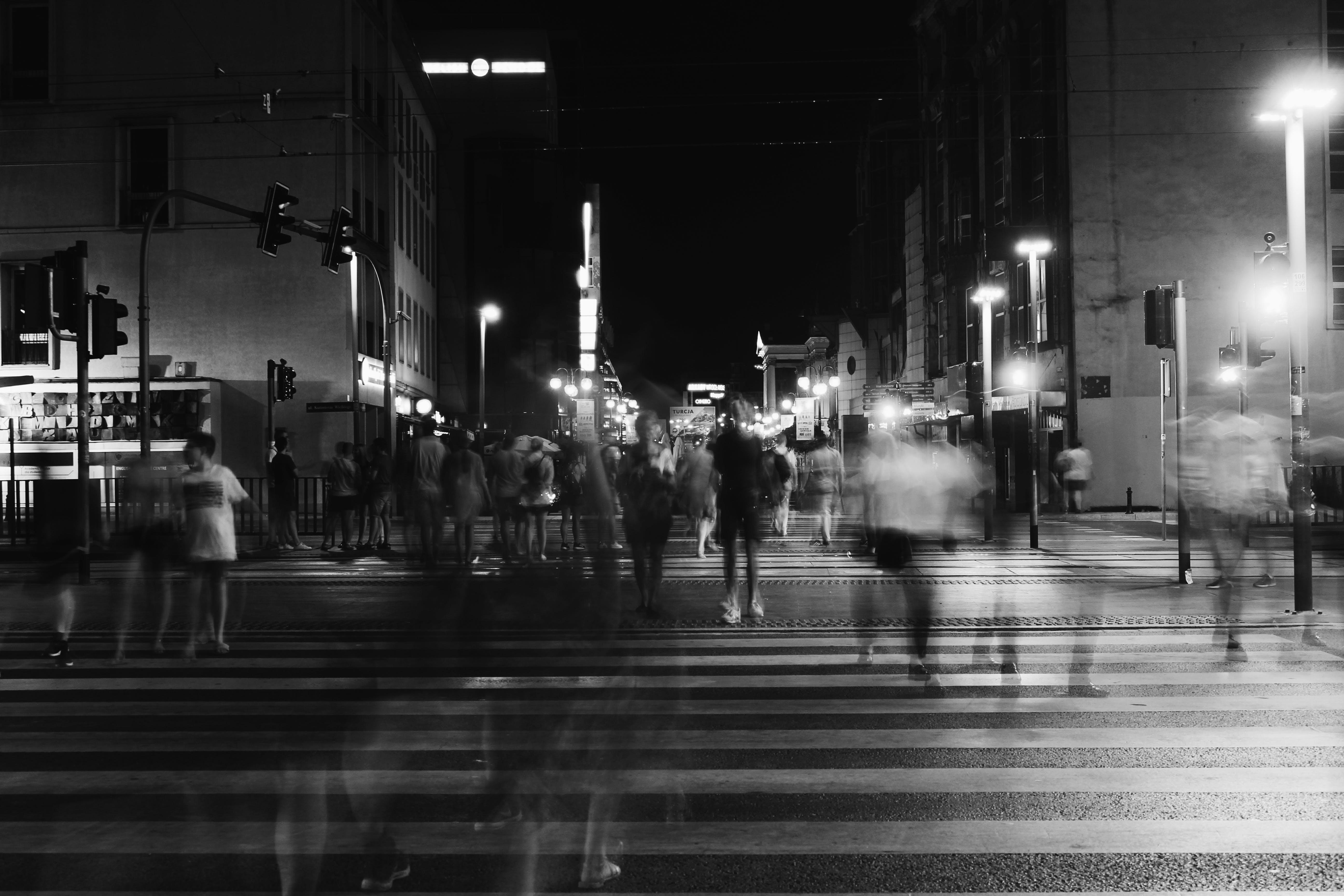 Group of People Crossing Pedestrian Lane in Greyscale