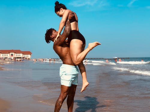 Man Lifting Woman on Seashore
