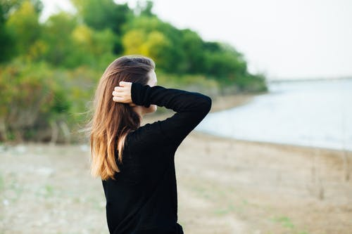 Woman Wears Black Long-sleeved Shirt Standing Near Body of Water