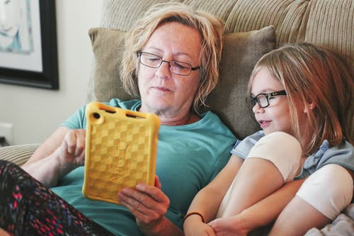 Woman Holding Tablet Lying Beside Girl Wear Eyeglasses