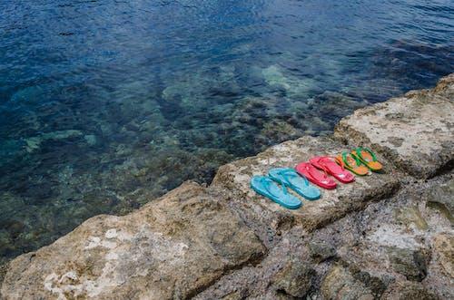Foto profissional grátis de água, beira-mar, chinelo, chinelos