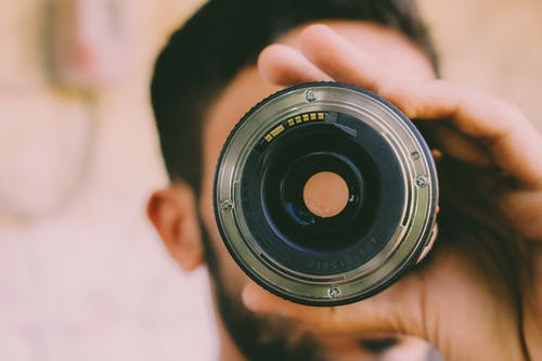 Selective Focus Photography of Man Holding Camera Lens