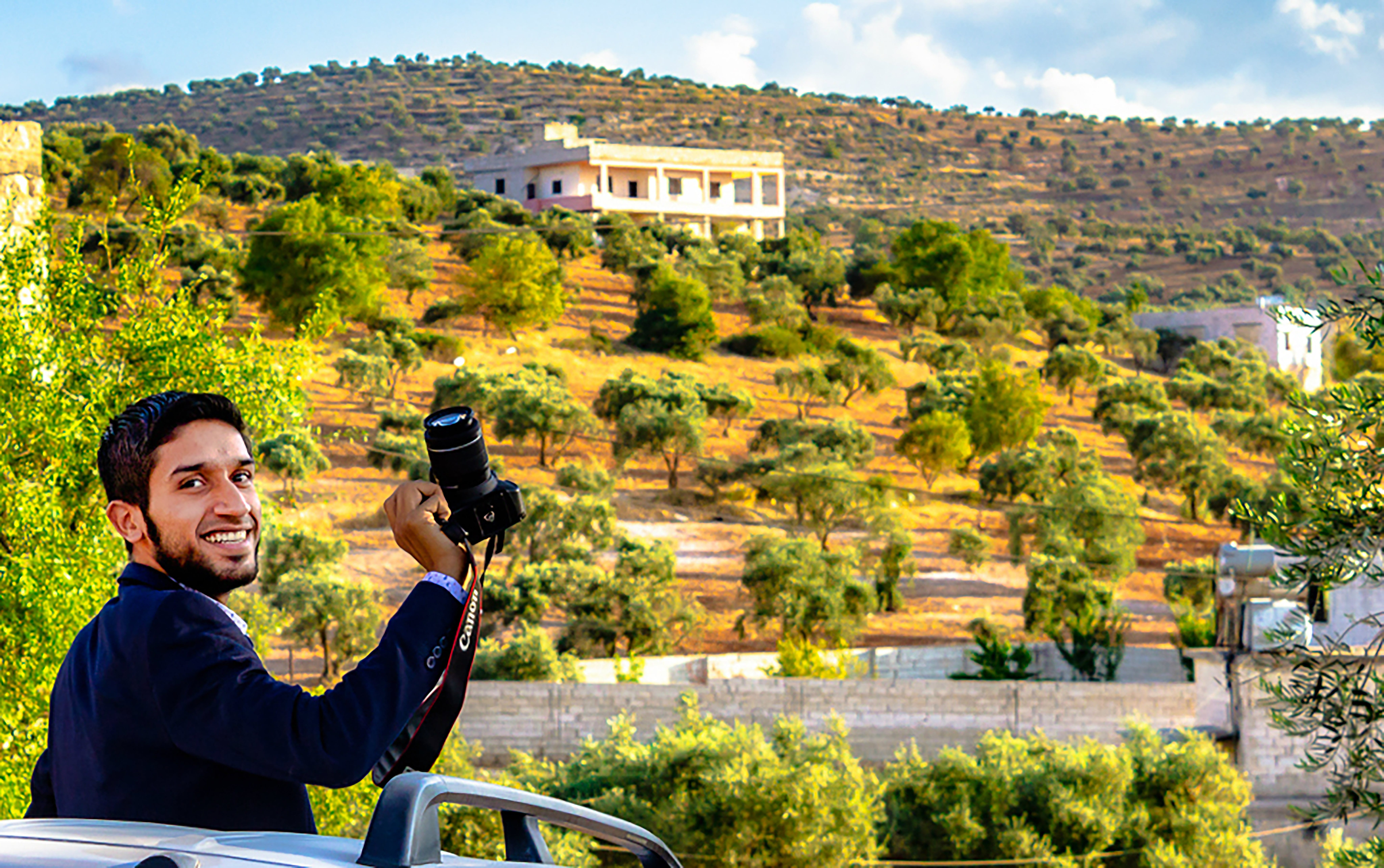 Smiling Man Holding Black Canon Dslr Camera in Front of Trees and Buildings