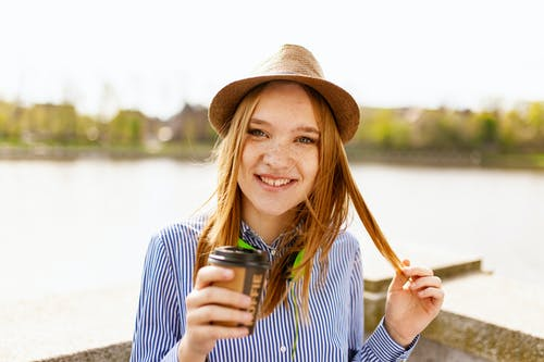 Smiling Woman Wearing White and Blue Striped Button-up Dress Shirt Holding Plastic Coffee Cup Standing Near Body of Water