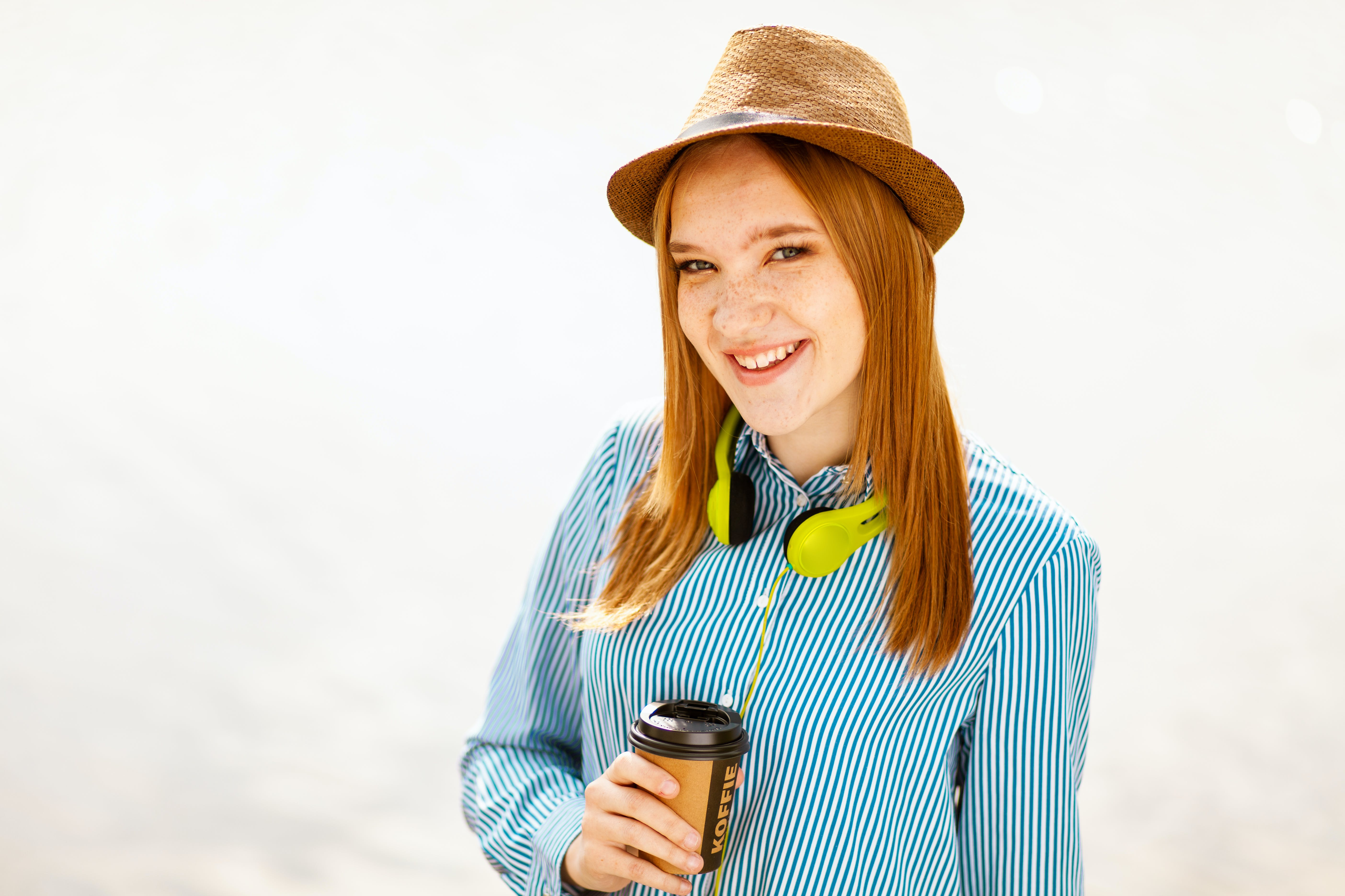 Smiling Woman Wearing Hat Holding Cup