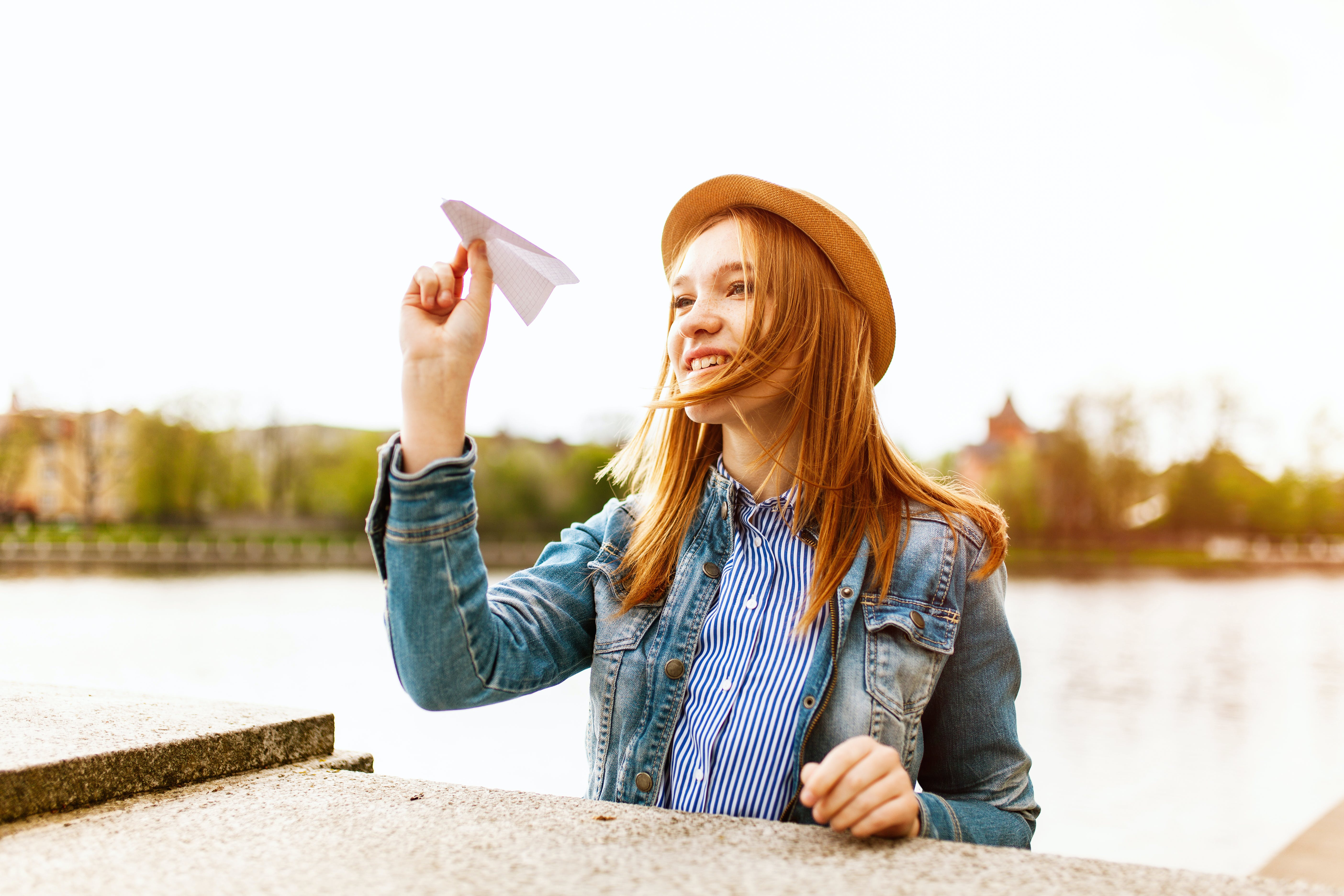 Woman in Blue Denim Button-up Jacket and Brown Hat About to Fly a Paper Plane Beside a Body of Water