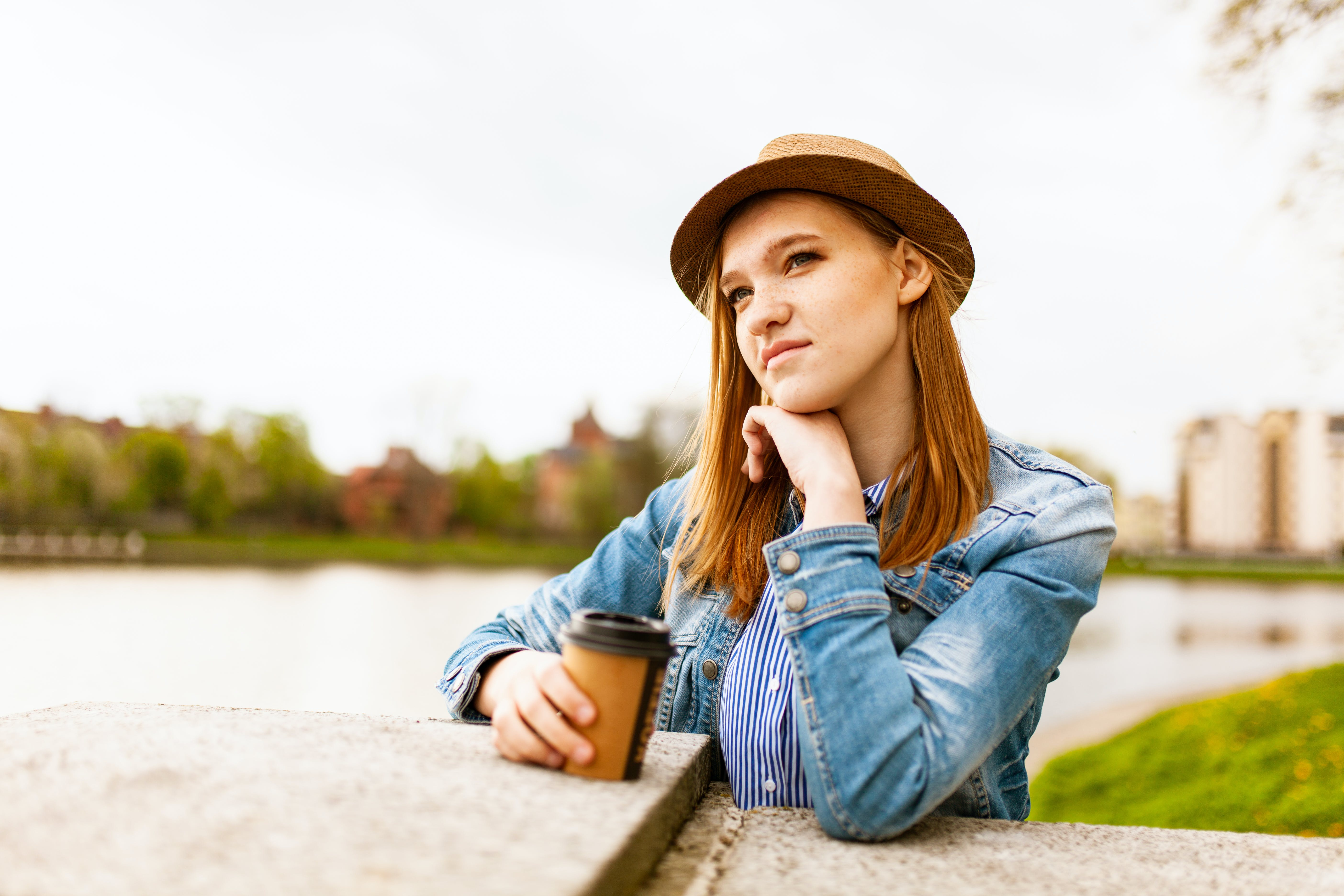 Woman Wearing Blue Denim Jacket Holding Coffee Cup Standing Near Concrete Platform