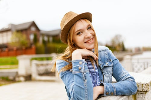Smiling Woman Wearing Blue Denim Button-up Jacket and Brown Hat With Hands Below Her Face