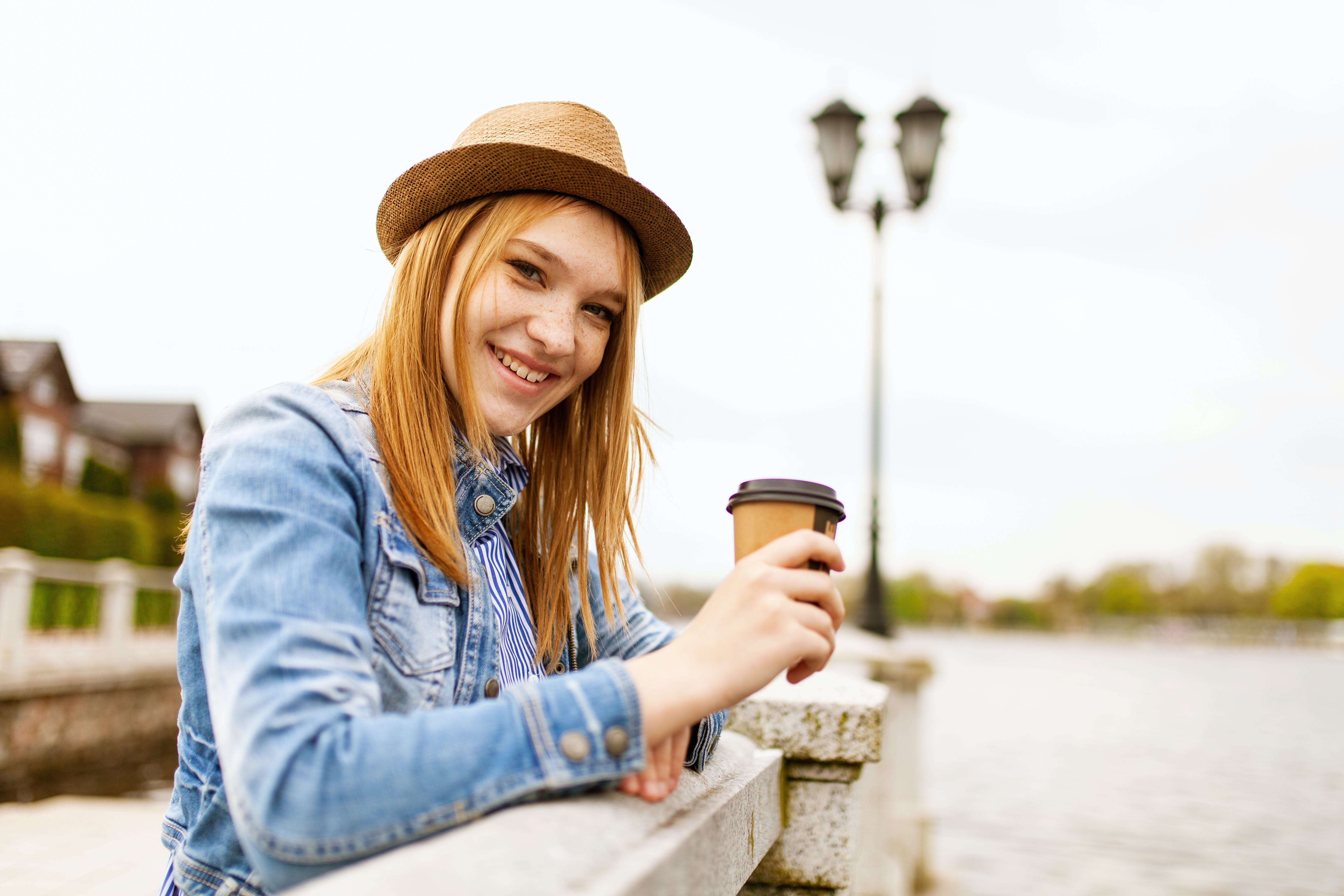 Woman Wearing Blue Denim Jacket While Holding Disposable Coffee Cup