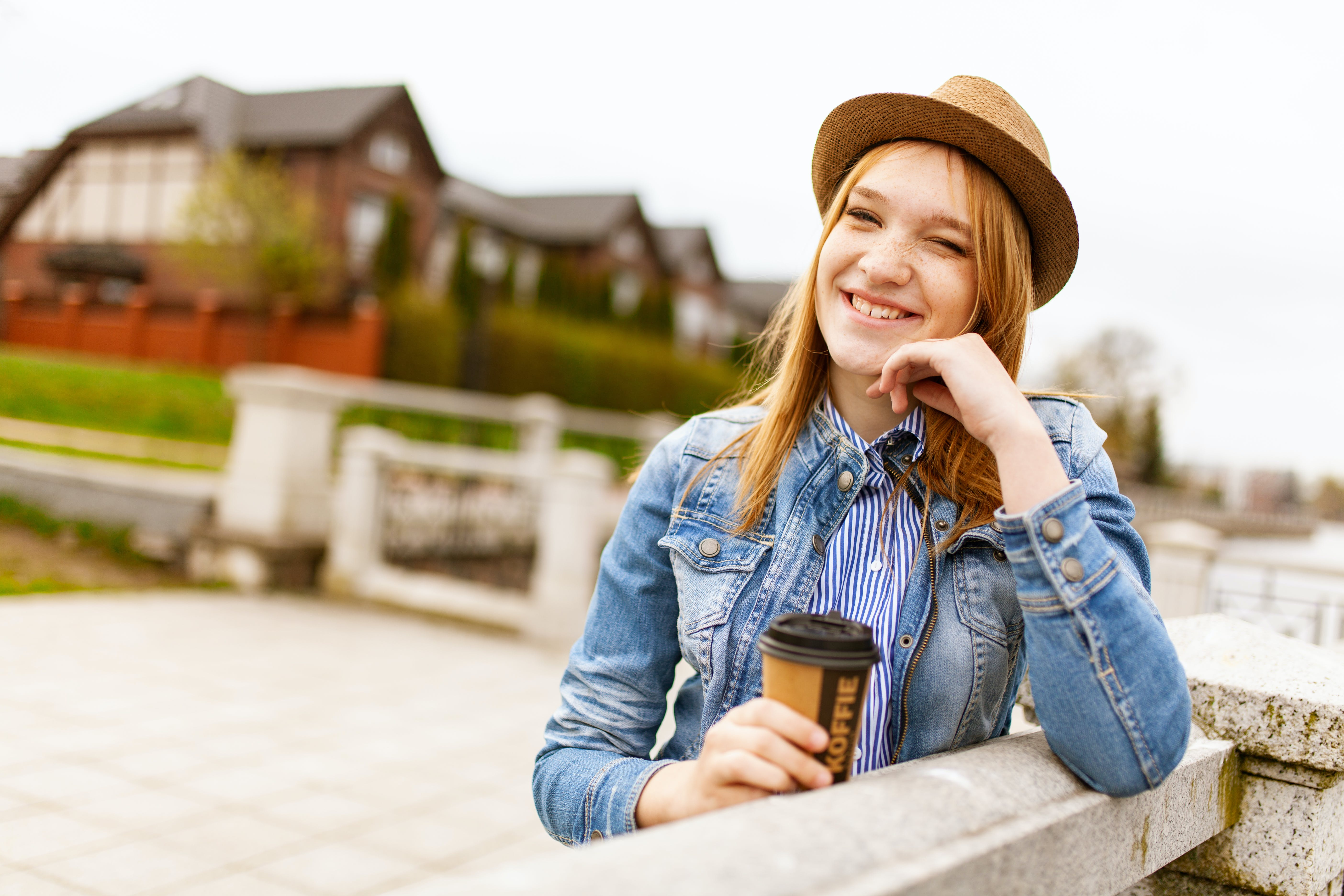 Woman Holding Cup of Tea Leaning on Fence