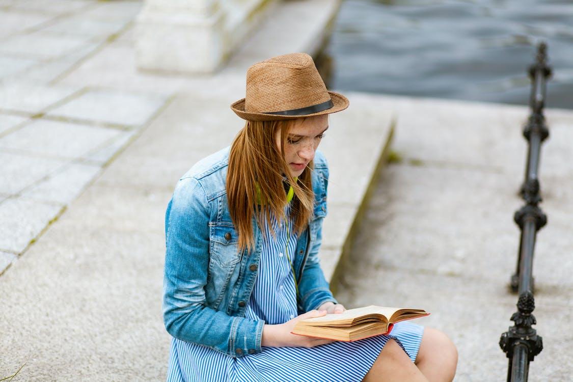 Woman Sitting on Grey Concrete Pavement Reading Book