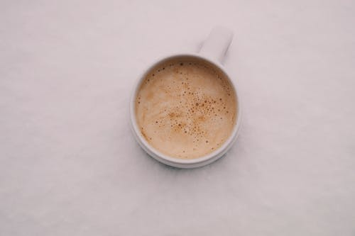 White Ceramic Cup Filled With Brown Liquid