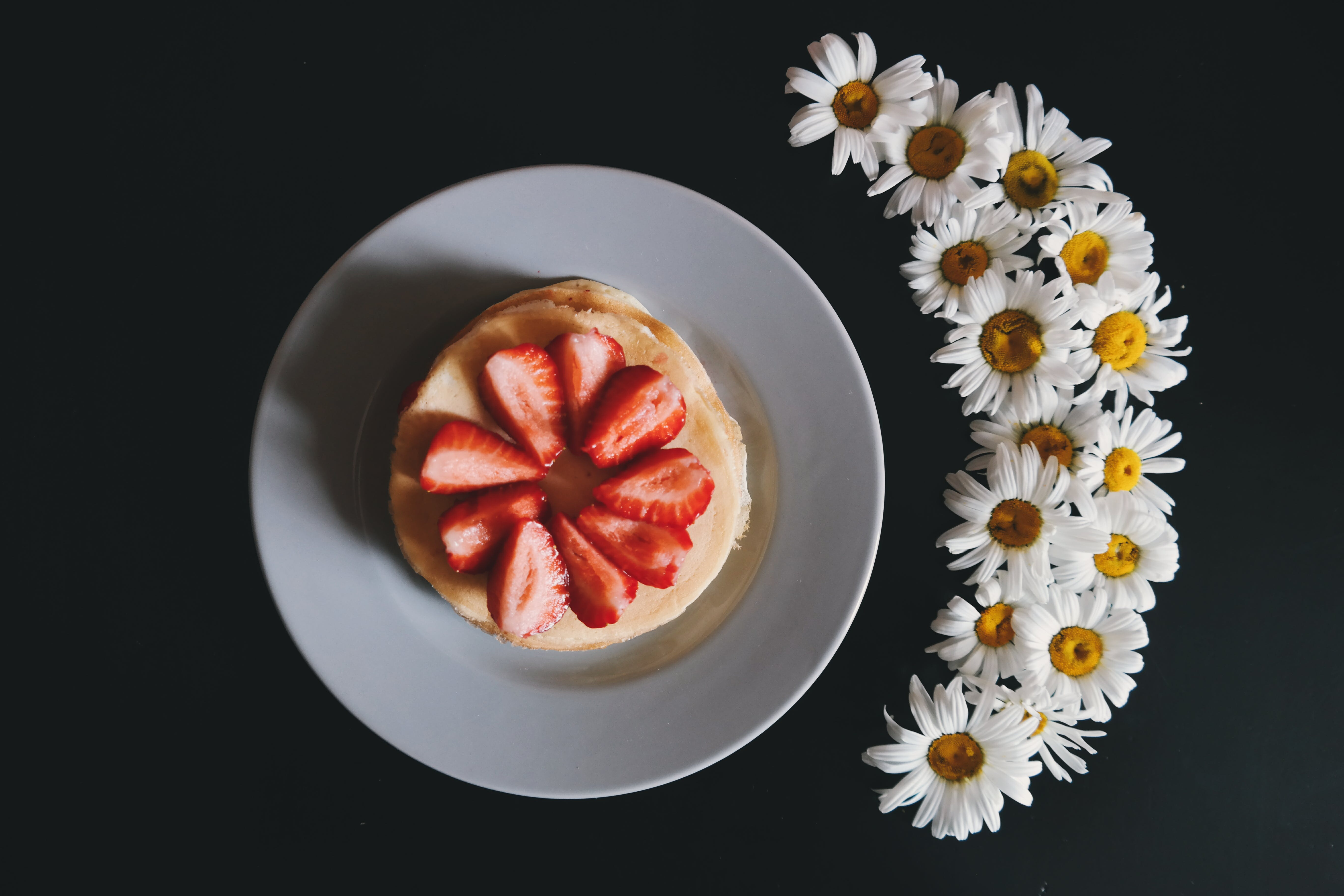 Round Pastry With Sliced Strawberries in White Plate