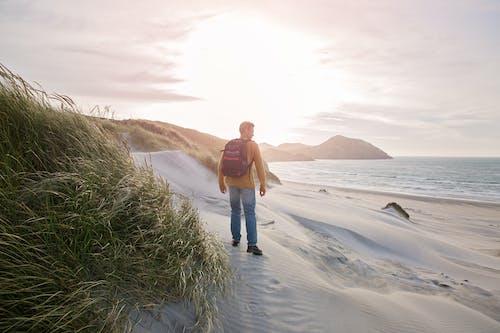 Man Carrying Black Backpack Standing on Seashore
